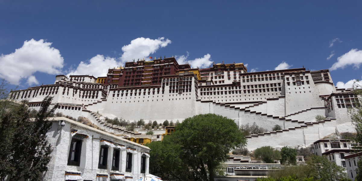 Potala Palace, a huge white fortress with many wooden shutters