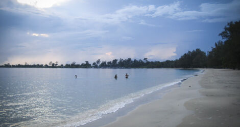 Beach in Cambodia with cloudy sky and people swimming in the sea