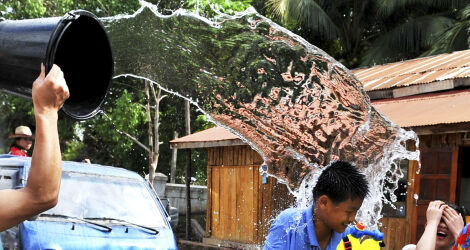 Bucket of water being thrown over a laughing boy in Laos