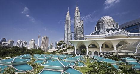 Futurist-looking glass city with Petronas Towers against blue sky, Malaysia