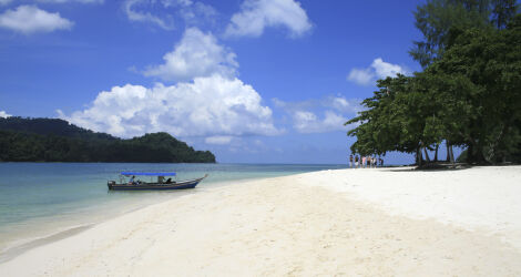 White sand, blue sea and sky and a little boat in Malaysia