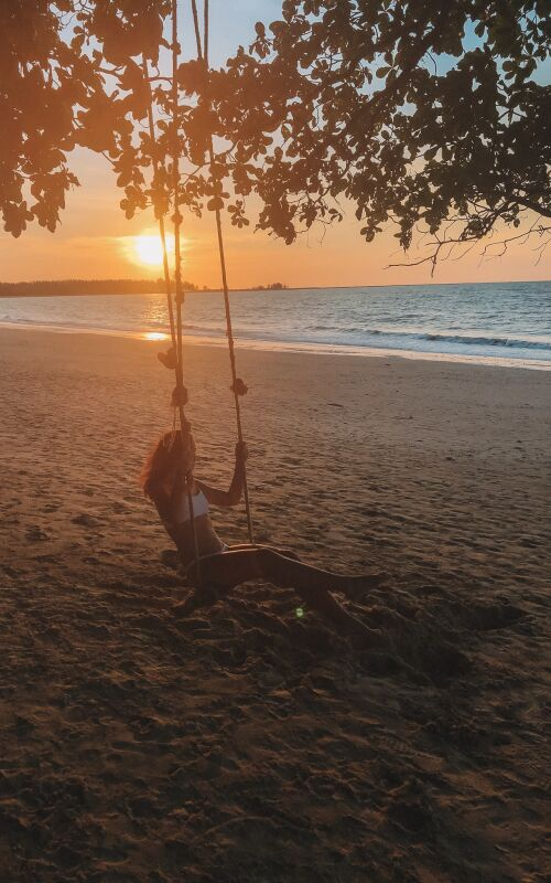 Honeymooner on beach swing at sunset in Thailand
