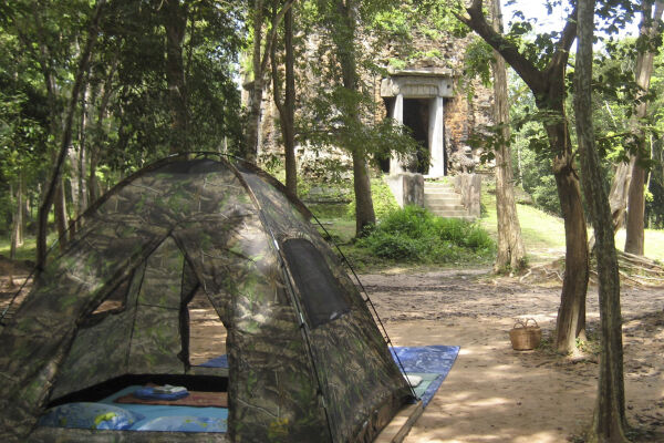 A light tent pitched in front of a Khmer ruin